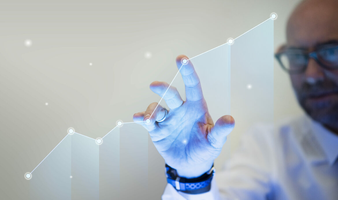 Businessman pointing his finger to a growth graph