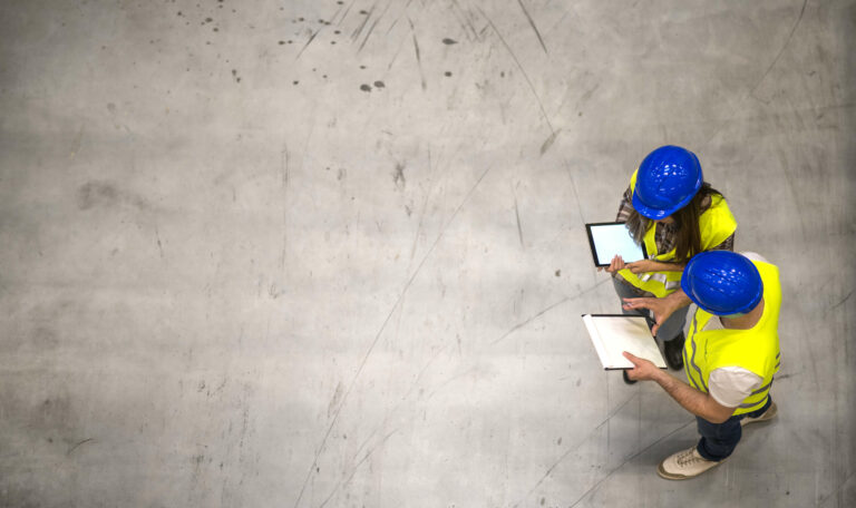 Top view of two industrial workers wearing hardhats and reflective jackets holding tablet and checklist on gray concrete background.