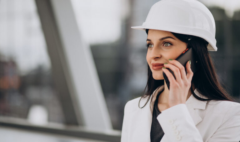 Young business woman wearing hard hat at building object